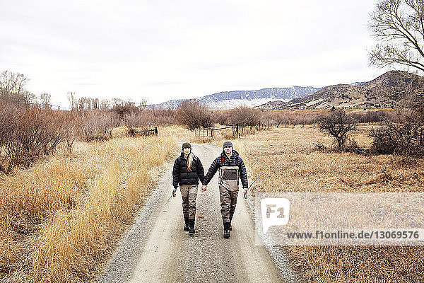 Couple holding hands while walking on footpath