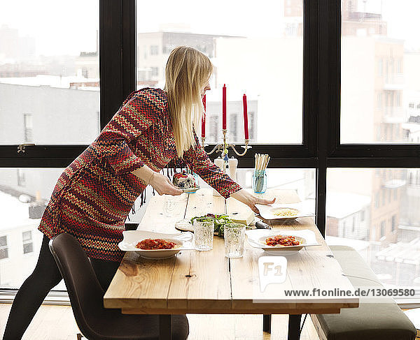 Frau arrangiert Essen am Esstisch zu Hause