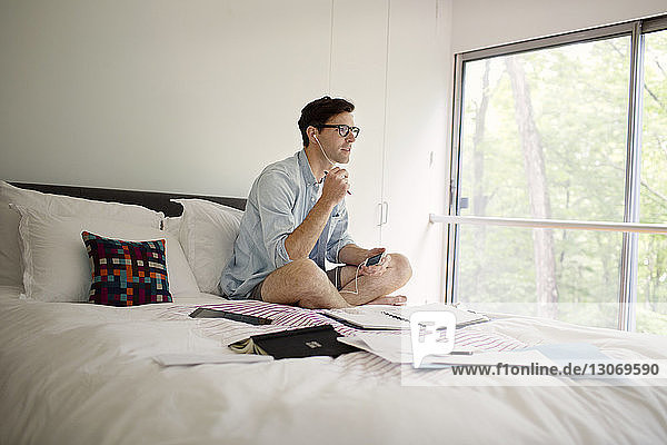 Man talking through headphones from phone while working on bed at home