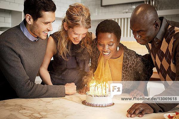 Glückliche Freunde schauen auf Geburtstagskuchen