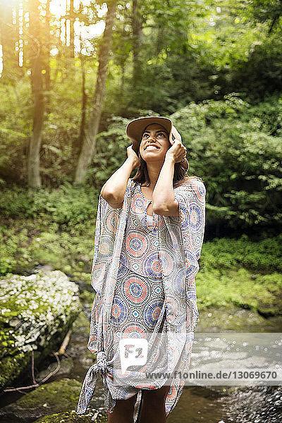 Frau mit Sonnenhut schaut im Wald stehend nach oben