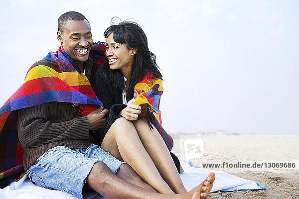 Frau sieht Mann an  während sie am Strand gegen den Himmel sitzt