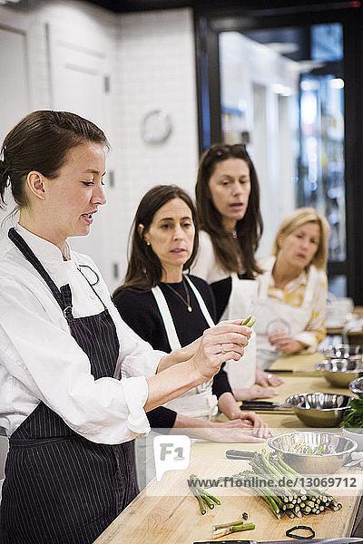 Frau unterrichtet Studenten im Kochkurs