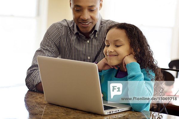 Father and daughter using laptop computer at home
