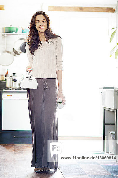 Porträt einer Frau  die Teekessel und Tasse hält