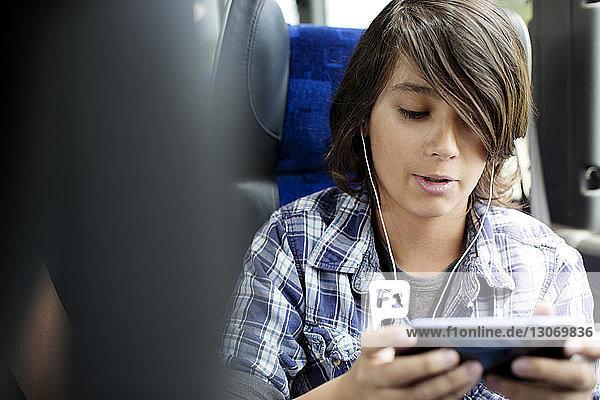 Junge hört Musik auf Tablet-Computer  während er im Bus sitzt