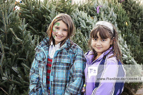 Portrait of happy sisters standing in backyard during winter