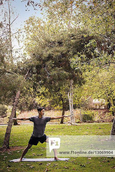 Sportler übt Kriegerpose auf Übungsmatte
