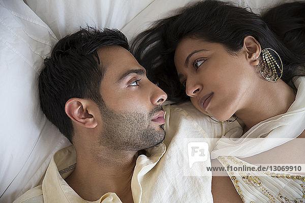 Draufsicht auf ein Paar  das zu Hause im Bett liegt