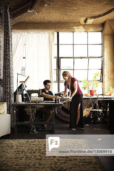 Modedesigner arbeiten mit Mitarbeiter gegen Fenster in einem Workshop