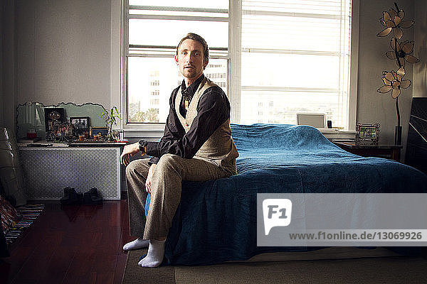 Portrait of man sitting on bed at home