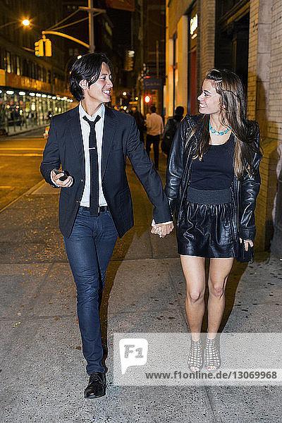 Glückliches Paar schaut sich an  während es nachts auf der Straße der Stadt steht
