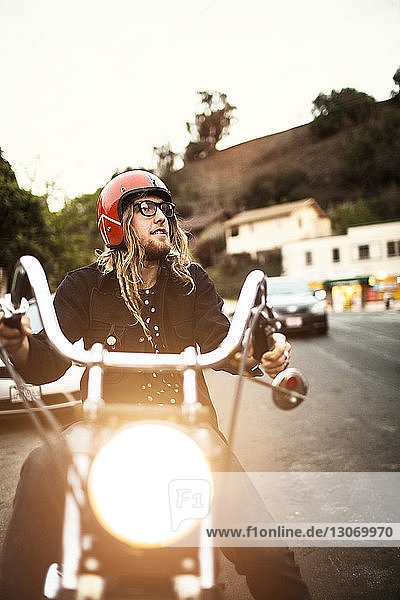Man looking away while riding motorcycle on street