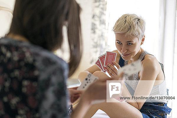 Freunde spielen Kartenspiel  während sie zu Hause sitzen
