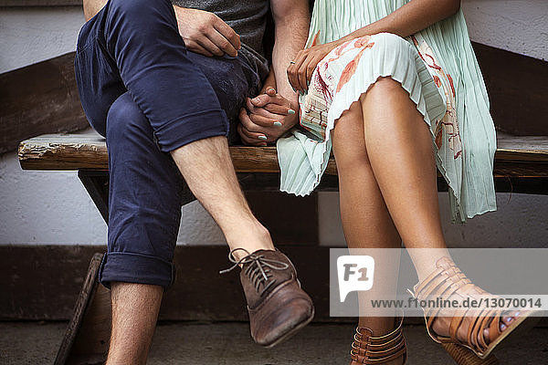 Low section of couple holding hands while sitting on bench