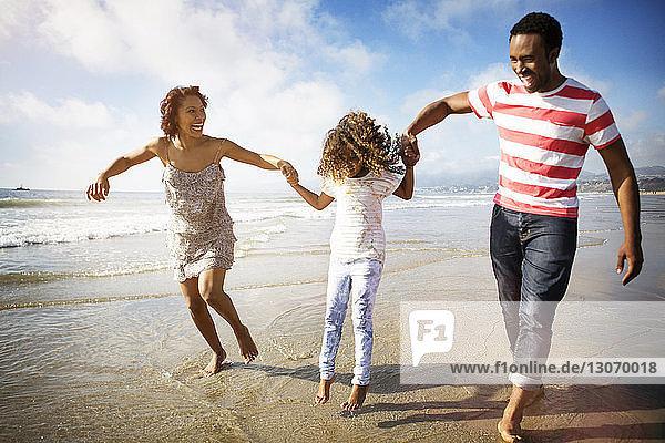 Verspielte Familie hält die Hände der Tochter  während sie sich am Strand am Ufer vergnügt