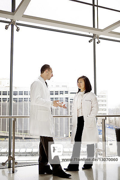 Doctors talking while standing by window in hospital