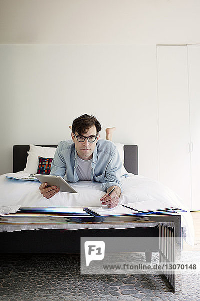 Portrait of man using tablet computer while working on bed against wall at home