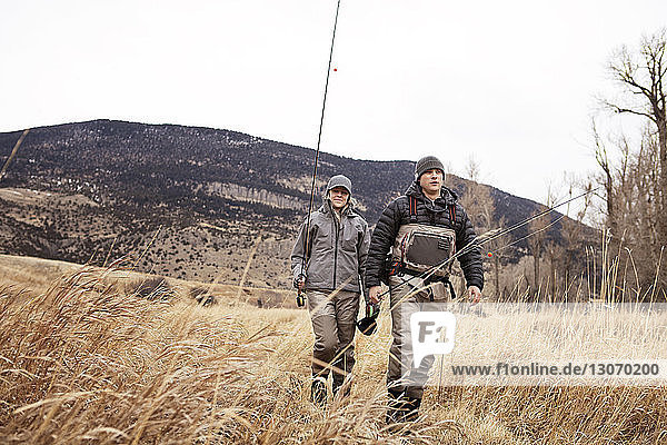 Couple holding fishing rods while walking on field
