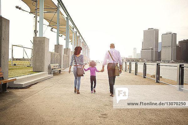 Rückansicht einer Familie  die auf einer Promenade in der Stadt bei klarem Himmel spazieren geht