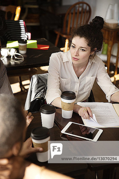 High angle view of woman with document talking to colleague at cafe