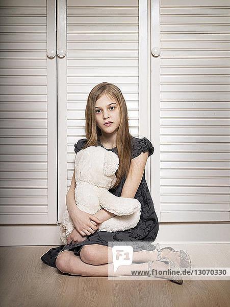 Porträt eines Mädchens  das einen Teddybär hält  während es zu Hause am Schrank sitzt
