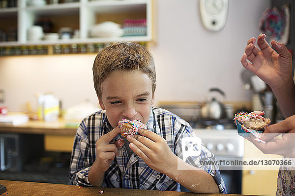 Boy eating cupcake while standing in kitchen
