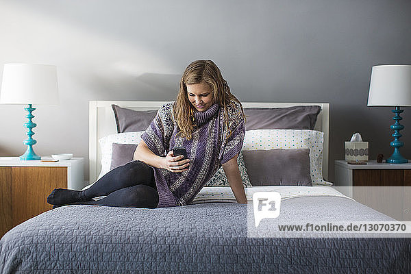 Woman using smart phone while sitting on bed at home