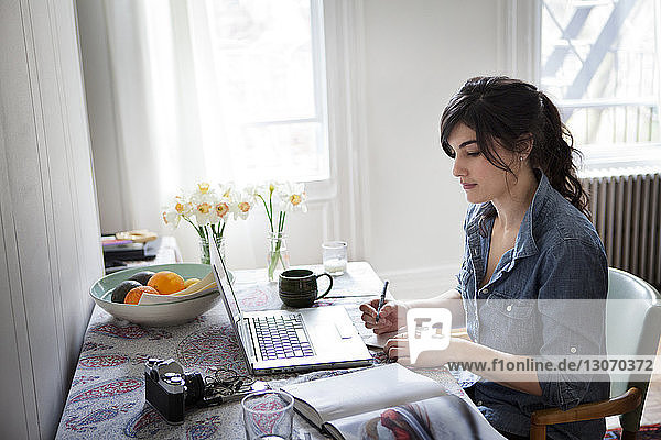 Woman with books and pen using laptop computer for searching recipe