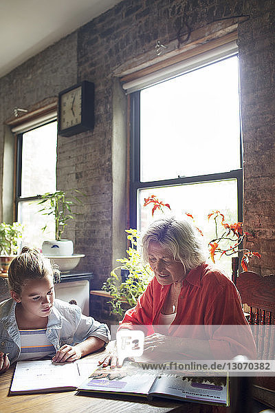 Woman explaining granddaughter while sitting at home