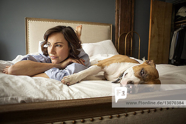 Woman with dog resting on bed at home