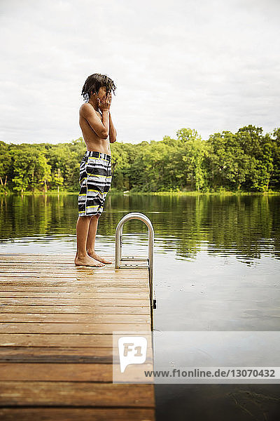 Side view of boy standing at dock