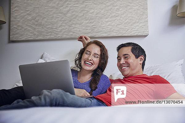 Fröhliches Paar betrachtet Laptop-Computer  während es zu Hause im Bett liegt