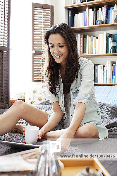 Happy woman using tablet computer on bed
