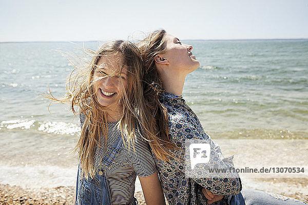 Glückliche Freunde stehen Rücken an Rücken gegen den Strand