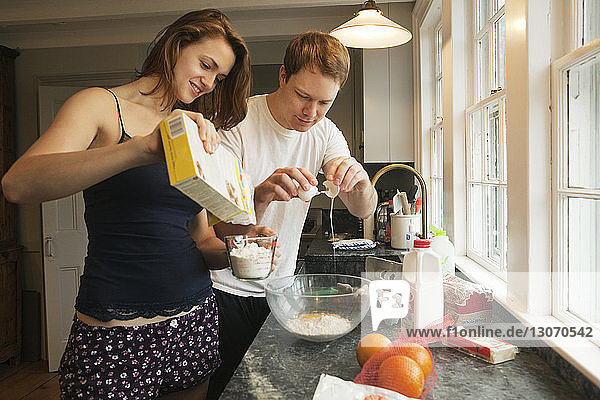 Happy couple preparing breakfast while standing at home