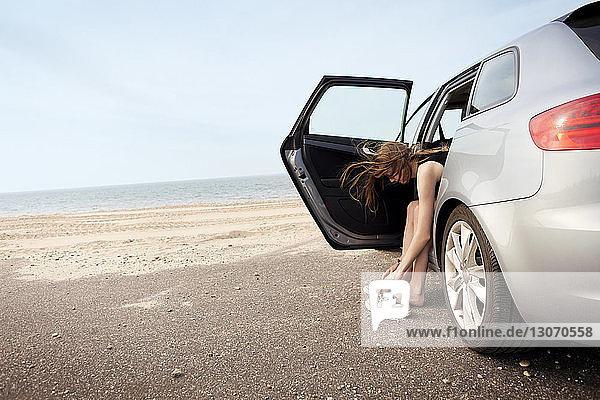 Frau trägt Schuhe  während sie am Strand im Auto sitzt