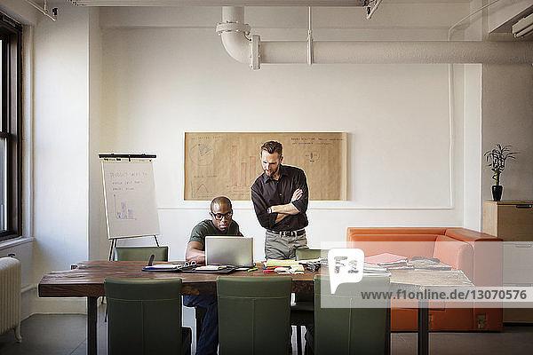 Geschäftsleute  die bei der Arbeit im Büro auf ihren Laptop schauen
