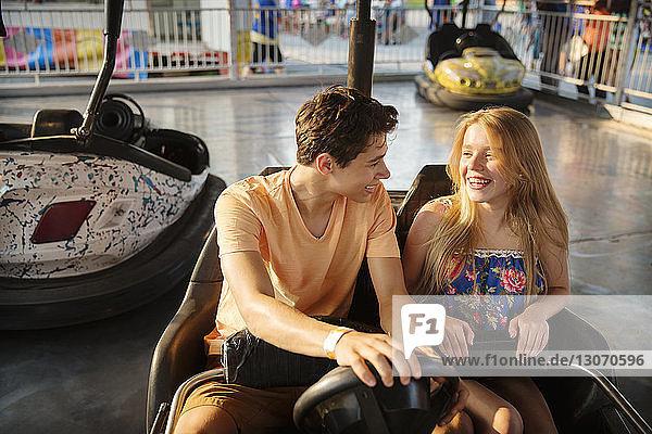 Happy couple riding bumper car at amusement park