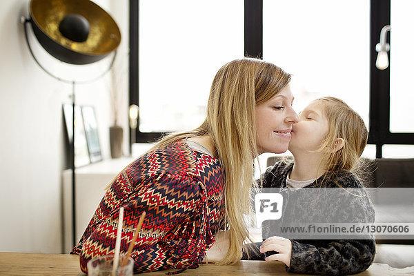Mädchen küsst Mutter  während sie zu Hause am Tisch sitzt