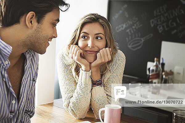 Smiling woman looking at man while leaning on table at home