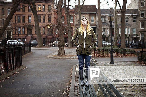 Woman standing on bench and looking up