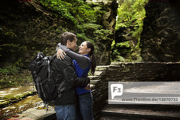 Side view of couple embracing while standing in forest