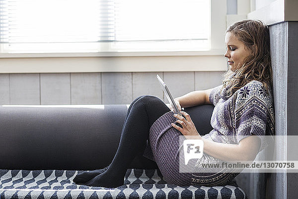 Side view of woman using tablet computer while sitting on sofa at home