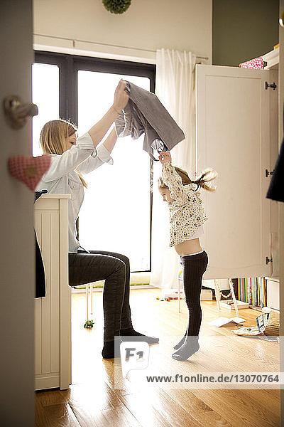 Mutter wechselt zu Hause das Kleid ihrer Tochter