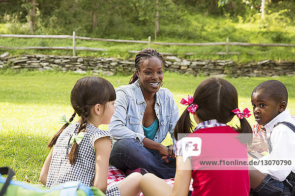 Teacher talking with students while sitting on field