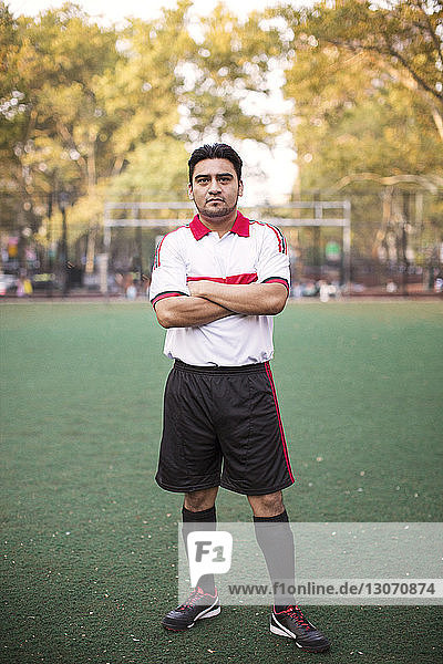 Portrait of soccer player with arms crossed at field