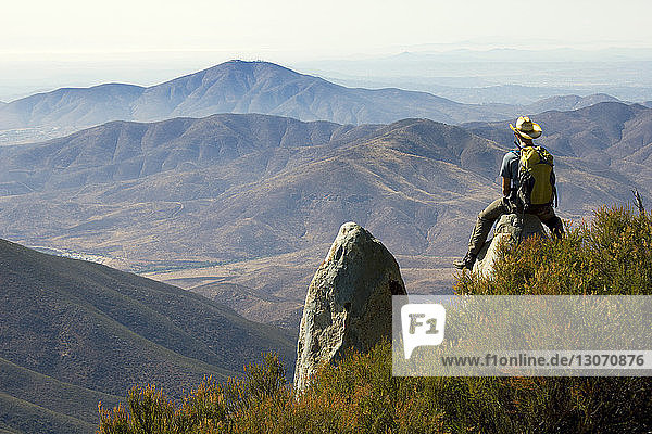 Rear view of man sitting on rock at mountain cliff