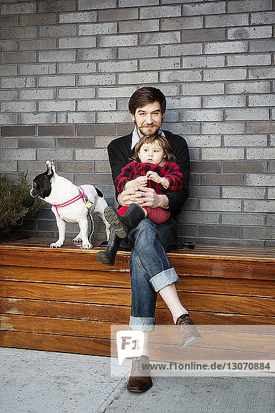 Portrait of man sitting with daughter on bench against wall