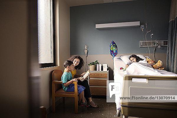 Mutter und Sohn lesen ein Buch  während sie im Krankenhaus auf einem Stuhl neben dem Patienten sitzen